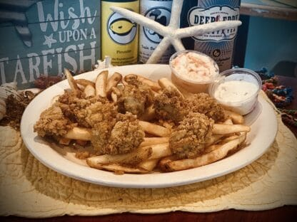 Fried oysters and seasoned French fries with coleslaw and Tartar sauce
